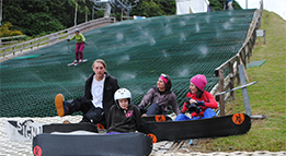 Snowboarders sitting with skier in background